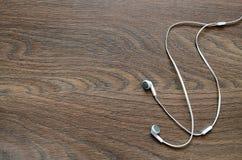 Écouteurs sur le fond en bois brun Photographie stock