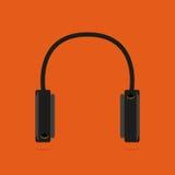 Écouteurs sur un fond orange Avec l'ombre Images stock