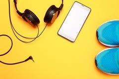 Écouteurs, téléphone intelligent et espadrilles bleues sur le fond jaune Image libre de droits