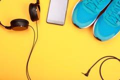 Écouteurs, téléphone intelligent et espadrilles bleues sur le fond jaune Images stock