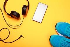 Écouteurs, téléphone intelligent et espadrilles bleues sur le fond jaune Image stock