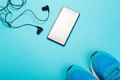 Écouteurs, téléphone intelligent et espadrilles sur le fond bleu Photos libres de droits