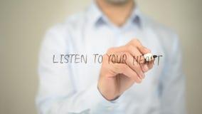 Écoutez votre coeur, écriture d'homme sur l'écran transparent Photographie stock libre de droits