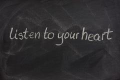 Écoutez votre coeur sur un tableau noir Photographie stock libre de droits