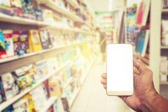Écran blanc de Smartphone à disposition sur la librairie brouillée Images libres de droits