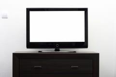 Écran blanc de TV sur la commode brune Images stock