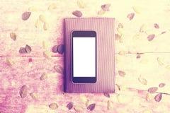 Écran blanc vide de smartphone sur le journal intime avec diar et les feuilles sur W Photo stock