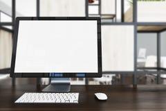 Écran d'ordinateur vide sur la table en bois foncée Photo stock