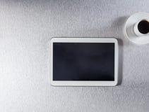 Écran de Blanck sur le comprimé numérique et le café sur le bureau métallique Images libres de droits