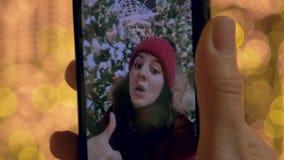 Écran de Smartphone sur lequel une femme prend une photo se tenant à la foire de Noël banque de vidéos