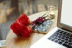 Écran et clavier d'ordinateur portable de plan rapproché sur la table en bois Les fleurs rouges de roses présentent pour le jour  Photos libres de droits