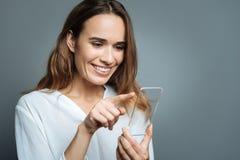 Écran sensoriel émouvant de femme heureuse gaie Photo stock