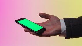 Écran vert sur le mobile barre Téléphone de participation de main du ` s d'homme d'affaires avec l'écran vert photographie stock libre de droits