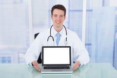 Écran vide de docteur Presenting Laptop With au bureau Images libres de droits
