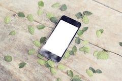 Écran vide de smartphone avec des feuilles sur la table en bois extérieure Images stock