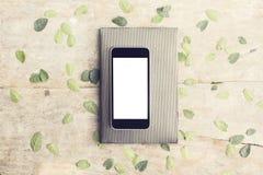 Écran vide de smartphone avec les feuilles et le journal intime sur la table en bois Images stock