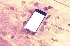Écran vide de smartphone sur la table en bois avec des feuilles Image libre de droits