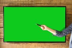 Écran vide de TV pour des présentations Main du ` s de femme indiquant l'écran Photographie stock libre de droits