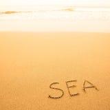 Écrit à la main en sable sur une plage de mer Photographie stock