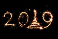 2019 écrit avec le feu d'artifice d'étincelle sur le fond noir, Ne heureux photographie stock