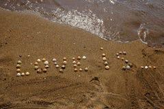 Écrit sur le sable avec des coquilles Photographie stock