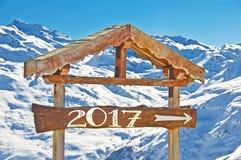 2017 écrit sur un signal de direction en bois, paysage de montagne de neige Photographie stock libre de droits
