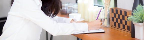 Écriture asiatique de jeune femme d'affaires de site Web de bannière de plan rapproché sur le carnet sur la table image stock