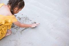 Écriture asiatique mignonne de fille d'enfant dans le sable et jouer sur la plage Photos stock