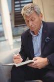Écriture attentive d'homme d'affaires dans l'organisateur image stock