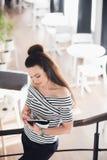 Écriture attrayante de jeune femme dans son carnet tout en se tenant sur des escaliers dans un café et regardant vers le bas Photos stock