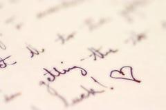 Écriture avec un coeur Photographie stock libre de droits