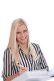 Écriture blonde de femme dans la reliure avec le stylo Photo stock