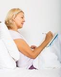 Écriture blonde de femme dans le carnet Image libre de droits