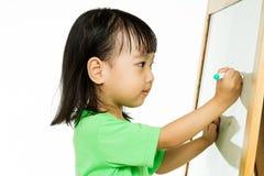 Écriture chinoise de petite fille sur le tableau blanc Images stock