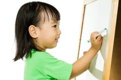 Écriture chinoise de petite fille sur le tableau blanc Photographie stock libre de droits
