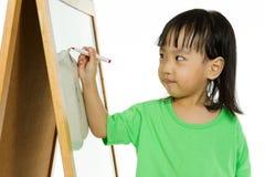 Écriture chinoise de petite fille sur le tableau blanc Photographie stock