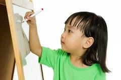 Écriture chinoise de petite fille sur le tableau blanc Images libres de droits