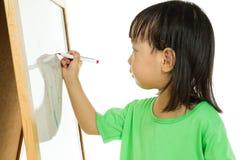 Écriture chinoise de petite fille sur le tableau blanc Image libre de droits