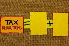 Écriture conceptuelle de main montrant des abattements fiscaux La réduction de présentation de photo d'affaires sur l'argent de l Photo libre de droits