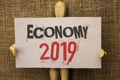 Écriture conceptuelle de main montrant l'économie 2019 Les revenus financiers du marché de croissance de devise des textes de pho Image libre de droits