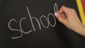 Écriture d'étudiant sur le grand tableau noir à l'école, de nouveau à l'école, le premier septembre banque de vidéos