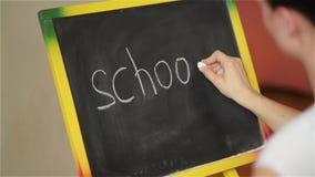 Écriture d'étudiant sur le grand tableau noir à l'école, de nouveau à l'école, le premier septembre clips vidéos