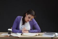 Écriture d'étudiante avec le livre dans le bureau de salle de classe Image stock