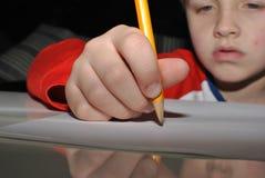 Écriture d'enfant avec le crayon Photographie stock libre de droits