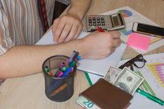 Écriture d'homme d'affaires dans un carnet Un homme d'affaires faisant quelques écritures utilisant sa calculatrice photos libres de droits