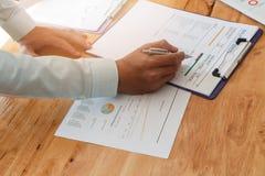 Écriture d'homme d'affaires ou pointage sur le papier de rapport images stock