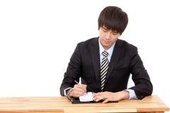 écriture d'homme d'affaires à un bureau avec un crayon lecteur Photos stock