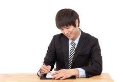 Écriture d'homme d'affaires à un bureau avec un crayon lecteur Image stock