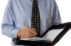 Écriture d'homme d'affaires dans l'organisateur en cuir Image stock