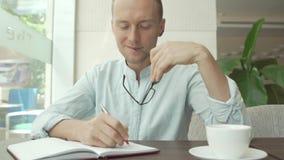 Écriture d'homme d'affaires dans le planificateur quotidien, journal intime photographie stock